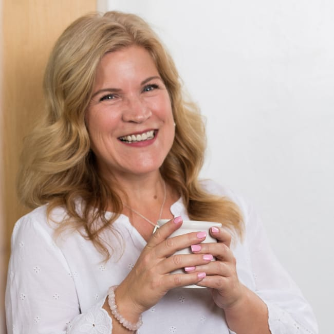 Deanna Moffitt smiling with a cup of coffee in a brightly lit room