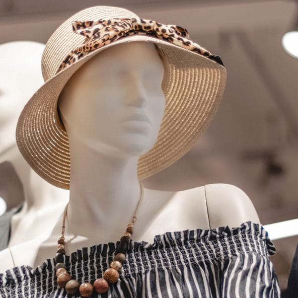 Close up of a female mannequin in a department store wearing a straw hat
