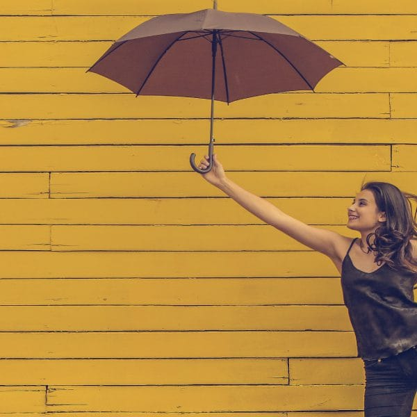 Woman holding an umbrella in front of a bright yellow background