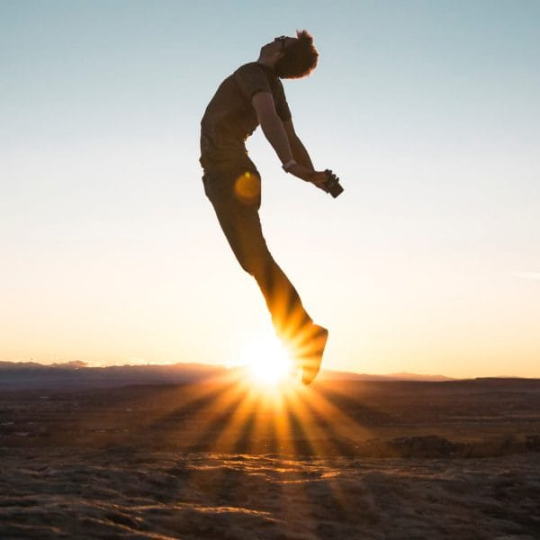 Man jumping high into the air with the sunset in the background