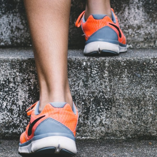 Close up image of a woman's running shoes as she runs up a flight of stairs
