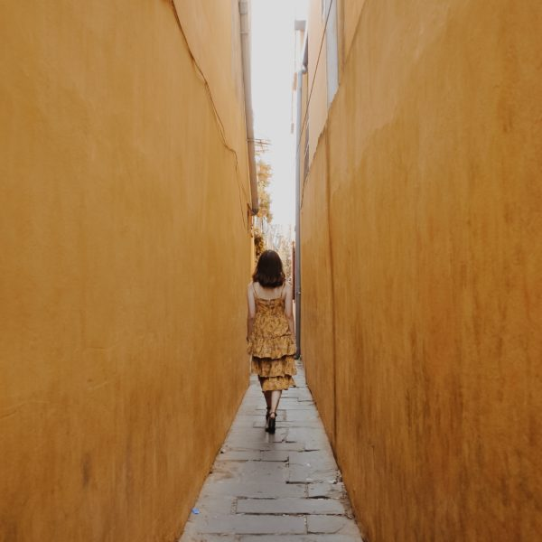 girl walking in yellow walls