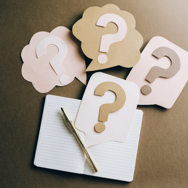 notebook with question marks and pen